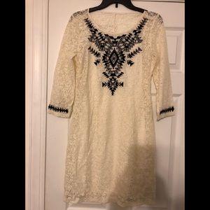 Cream dress with black pattern.